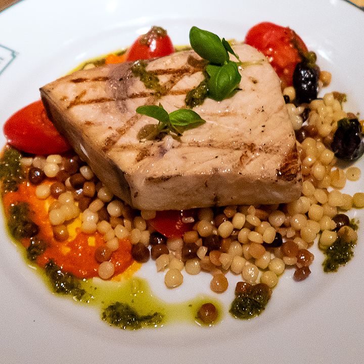 Swordfish with tomatoes, olives, pesto and giant couscous